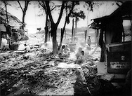 Children heat up breakfast with a wood and rubber tire fire at their Phnom Penh city dump settlement, Cambodia.