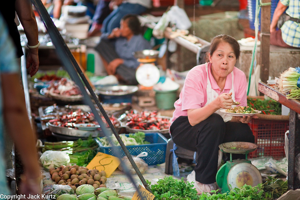 Mar. 24, 2009 -- A vendor finishes her breakfast in the market in Samut Sangkhram. The market is the end of the Mahachai Rail line and is built right on the tracks. When the train comes through, vendors fold up their stalls and move them off the rails only to open them again after the train passes.  The Mahachai Rail Line is a commuter line that runs from the Wong Wian Yai train station in the Thonburi section of Bangkok to the fishing port and market town of Samut Sakhon, which used to be known as Mahachai. An extension of the line runs from Baan Laem, near Samut Sakhon, to Samut Songkhram, another fishing port south of Samut Sakhon. Each stretch of the line takes about an hour.    Photo by Jack Kurtz