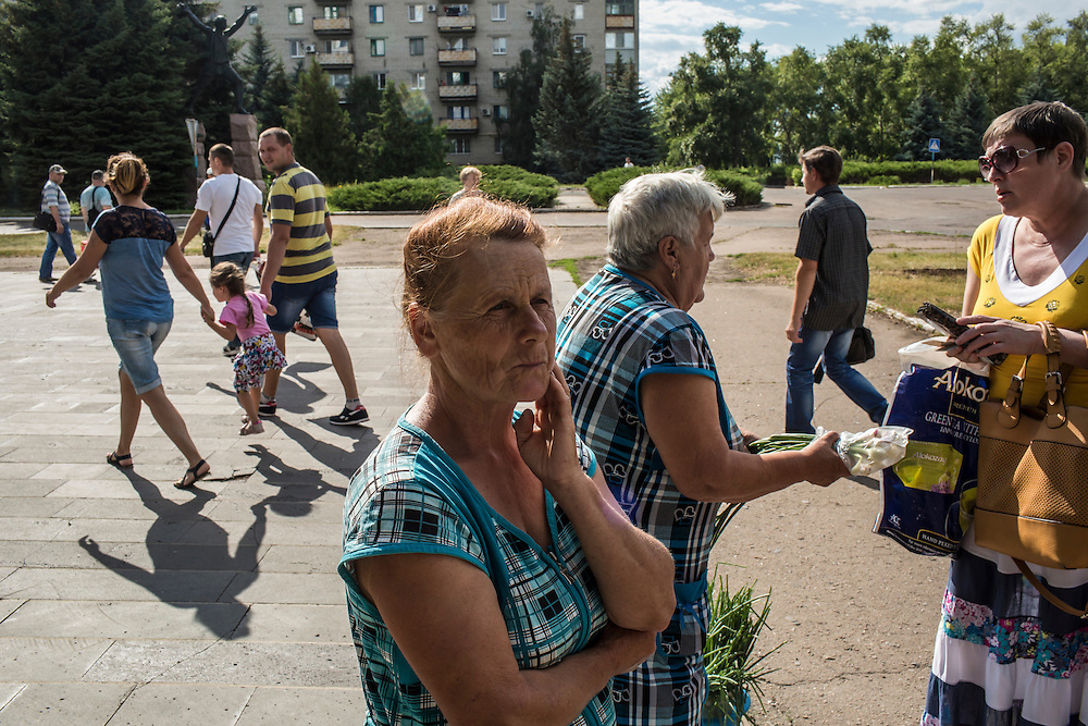 SVITLODARSK, UKRAINE - JULY 8, 2016: Women sell fruit and vegetables on the sidewalk in Svitlodarsk, Ukraine. The village is located less than ten miles from the front lines with rebel-controlled territory. CREDIT: Brendan Hoffman for The New York Times