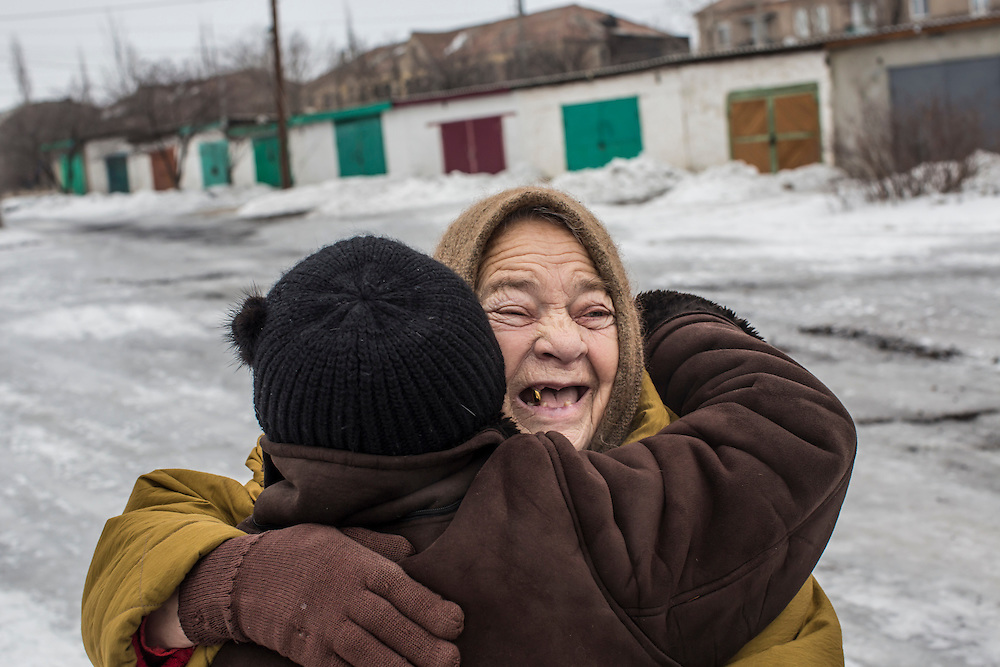KOMUNAR, UKRAINE - JANUARY 27, 2015: Galina Alekseyeva, 80, hugs Valentina, left, a volunteer who coordinates humanitarian aide for local residents and chose not to give her last name out of fear of repercussions, in Komunar, Ukraine. Like many local residents, Alekseyeva spent more than a month living in a basement when the village was the site of heavy fighting between pro-Russia rebels and Ukrainian forces over the summer. CREDIT: Brendan Hoffman for The New York Times