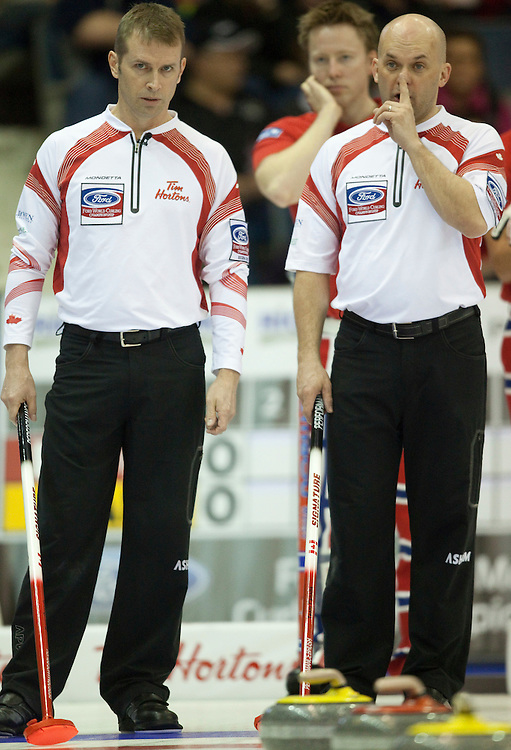 Canada's third Jon Mead, right, signals a nose hit as he and skip Jeff Stoughton discuss strategy during their match against Norway in the evening draw at the Ford World Men's Curling Championships at the Brandt Centre in Regina, Saskatchewan, April 7, 2011.<br /> AFP PHOTO/Geoff Robins
