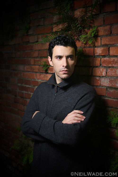 A Latino man leans confidently against a brick wall.