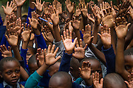 Hands raised by students at the Maroroni primary school in Arusha, Tanzania, to received donated text books.