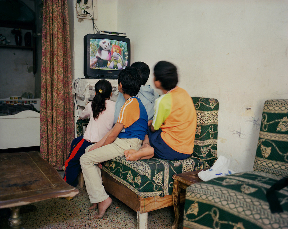 Fatin and Samir Kamil&rsquo;s children, unable to attend school, watch TV. Amman, Jordan<br />