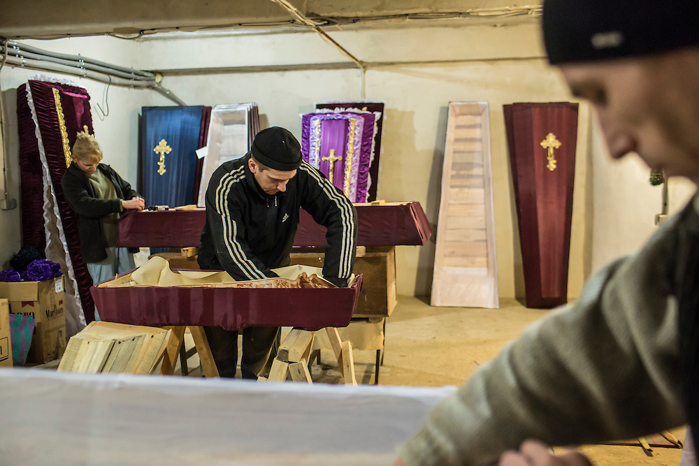 DONETSK, UKRAINE - FEBRUARY 3, 2015: Lyudmila Levochko, Pavel Bocharov, and Sergei Levohko, from left, build caskets in Donetsk, Ukraine. The city government provides basic but free or low-cost caskets for victims of shelling or others who are no longer able to afford funeral expenses, the demand for which has increased significantly in past weeks as violence has flared once again. CREDIT: Brendan Hoffman for The New York Times