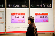 A man walks past an electric signboard indicating Japanese stock prices and other financial information February 3, 2009. The benchmark Nikkei 225 stock average lost 257.19 points, or 3.1 percent, to 7,994.05 Friday, with a trio of factors rattling investors: an overnight decline on Wall Street, weak economic data and dismal corporate earnings forecasts.