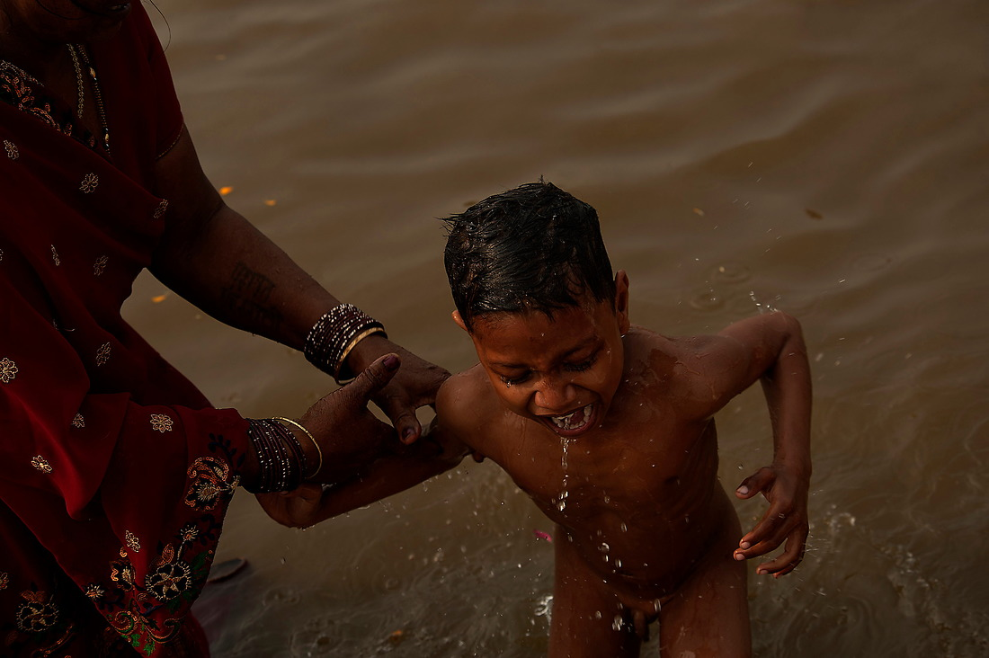"""A young child is dunked into the Ganges on February 6, 2013 in Allahabad, India during the Kumbh Mela. """"Kumbh Mela"""" is a mass Hindu pilgrimage of faith in which Hindus gather to bathe in a sacred river. — © Jeremy Lock/"""