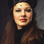 Lesa looks into the camera with her dark eyes wearing a high neck black dress and a black vintage hat with a bow and a veil over her face.