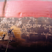 At the Norfolk Shipbuilding and Drydock Corporation, a painter sprays a rust damaged cargo vessel.