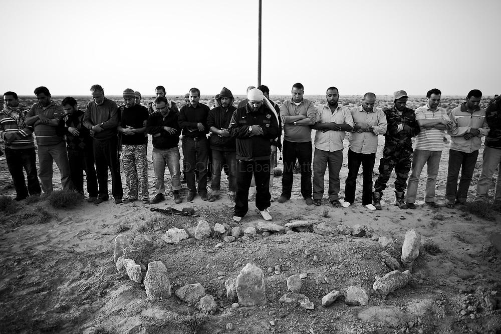 Sur la route entre Ras Lanouf et Brega, le 27 mars 2011, des insurgés prient devant la tombe de leurs compagnons tués et enterrés à la hâte par des soldats kadhafistes avant leur fuite.