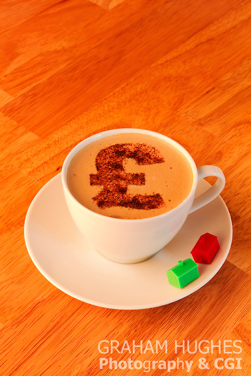 Coffee cup with monopoly houses on side of saucer. Pound symbol shape in chocolate topping. Cappuccino Effect.