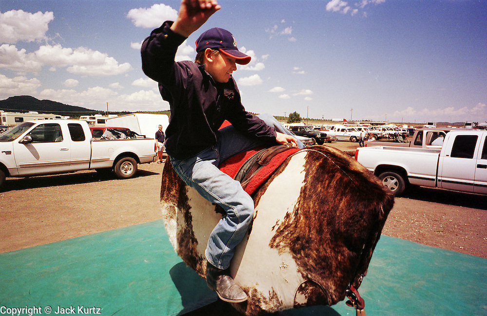 WIL2000080502 - 05 AUGUST 2000 - WILLIAMS, AZ: Hugh Campbell, 12, from Seligman, Arizona, rides a mechanical bucking bull at the 22nd Annual Cowpunchers' Reunion Rodeo in Williams, Arizona, Aug 5. The rodeo is held for working cowboys from the ranches in Arizona and the region. PHOTO BY JACK KURTZ