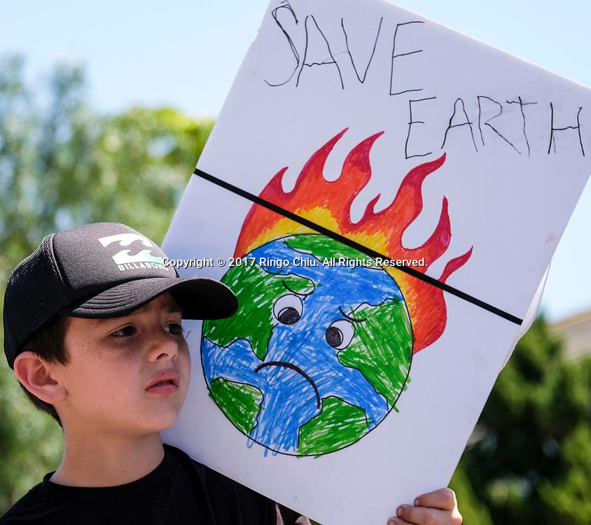 4月29日,美国加利福尼亚州洛杉矶,民众手示威牌参与「人民气候游行」。当天,美国多个城巿有民众趁总统特朗普就任一百日上街游行,反对特朗普对气候变化的态度。新华社发 (赵汉荣摄)<br /> A boy holding a sign participates in a climate change awareness march and rally, in Los Angeles, the United States, Saturday, April 29, 2017. The gathering was among many others of its kind held nationwide marking President Donald Trump's 100th day in office. (Xinhua/Zhao Hanrong)(Photo by Ringo Chiu/PHOTOFORMULA.com)<br /> <br /> Usage Notes: This content is intended for editorial use only. For other uses, additional clearances may be required.
