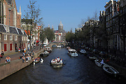 People take their boats down a canal on a beautiful hot October day in Amsterdam