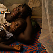 """Mariam Ouedraogo (22) and her daughter, Rachidatu Ouedraogo (3) under the mosquito net they share at their home in the village of Bore in the Sanmatenga region of Burkina Faso on 24 February 2014. Mariam says that since they have had the net she has """"noticed a big difference, because before I couldn't even sleep because of the mosquitos. But now the mosquitos no longer bite me because I sleep under a net."""" Mosquito nets greatly decrease the incidence of malaria by reducing the risk of being bitten by the nocturnal Anopheles mosquito, which carries the malaria parasite."""