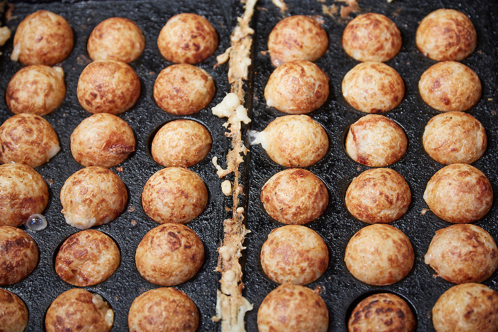 Takoyaki are a batter made of wheat flour filled with octopus, green onion, pickled ginger and tempura scraps. They are cooked in a special pan, and served with a choice of different sauces. They are considered a must-eat street food in Osaka.