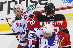 May 25, 2012; Newark, NJ, USA; New Jersey Devils defenseman Anton Volchenkov (28) hits New York Rangers right wing Ryan Callahan (24) during the second period in game six of the 2012 Eastern Conference finals at the Prudential Center.