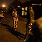 A police officer gestures to a man on a street in the slum of Korogocho during a night patrol.