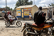 A moto taxi waits for a customer, while one with a family drives by on a dirt road in Leogone, Haiti. Leogone was near the epicenter of the 2010 earthquake that rocked Haiti, destroying much of the infrastructure. The country was already struggling with severe poverty and was left devastated in the aftermath.