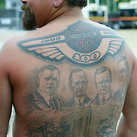 Mark Penticoff of Shannon, Illinois shows off his tattoo showing the four founders of the Harley-Davidson motorcycle company in downtown Milwaukee August 31, 2003.  Today was the final day of the legendary American motorcycle firm's 100th anniversary celebration.  The artwork on Penticoff's back took over 80 hours to produce.   REUTERS/Rick Wilking