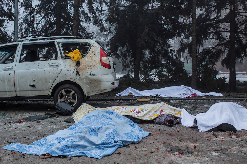 DONETSK, UKRAINE - JANUARY 30, 2015: The bodies of four people who were killed when a rocket struck the parking lot outside a center where humanitarian aid was being distributed lie on the ground in Donetsk, Ukraine. A fifth person was killed in a parked car, and at least two others died in a separate shelling nearby. CREDIT: Brendan Hoffman for The New York Times