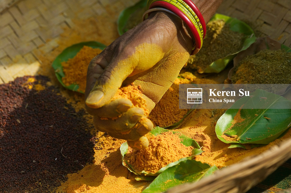 Hill tribespeople putting spices on leaves at Paraja market, Orissa, India