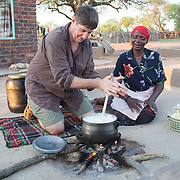 Bill Campbell, a cultural tourist, staying in the Venda village, cooks pap over a fire under the instruction of a Venda woman. Venda cultural group. Hamakuya. Venda village in Limpopo Province, South Africa.