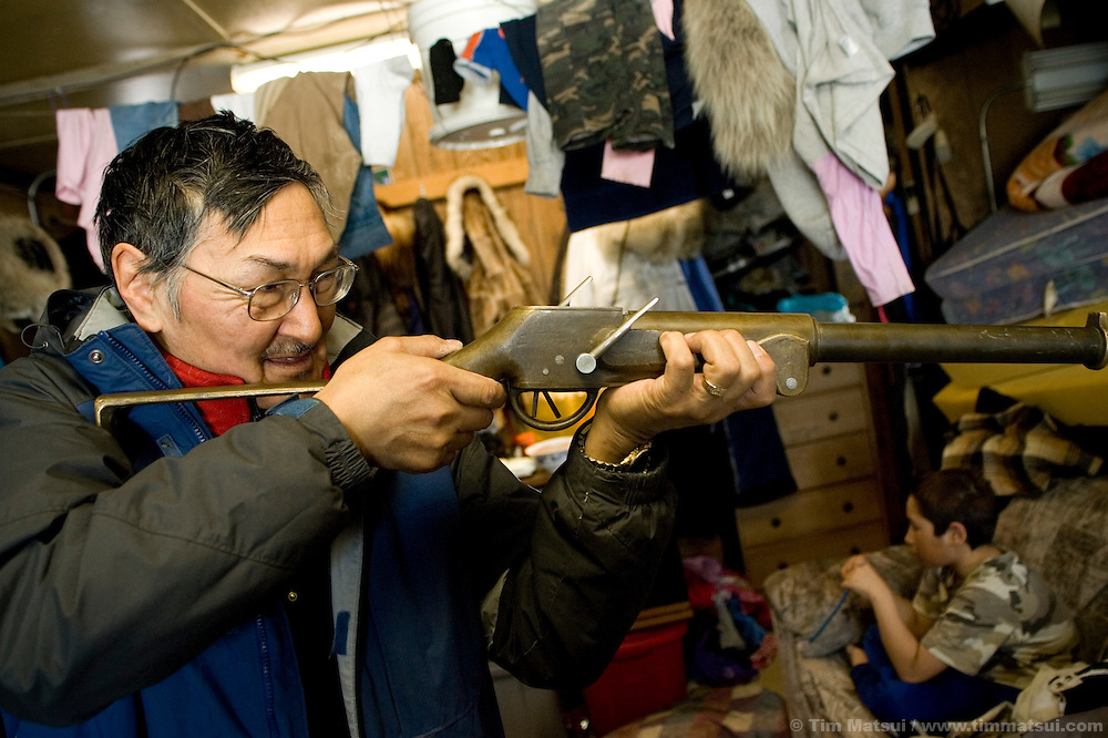 May 1, 2008 -- Kivalina, AK, U.S.A..Austin Swan discusses whale hunting weaponry and technique at his home in Kivalina, Alaska, while his adoptive son, 9 year old Justin Cooper Swan, watches TV. Kivalina is suing 20 oil companies for property damage related to global warming; the ocean pack ice forms later and melts earlier, leaving the town vulnerable to erosive winter storms and endangering their traditional subsistence lifestyle. (Photo by Tim Matsui)