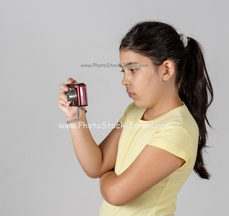 Young girl of 9 concentrating on a digital camera