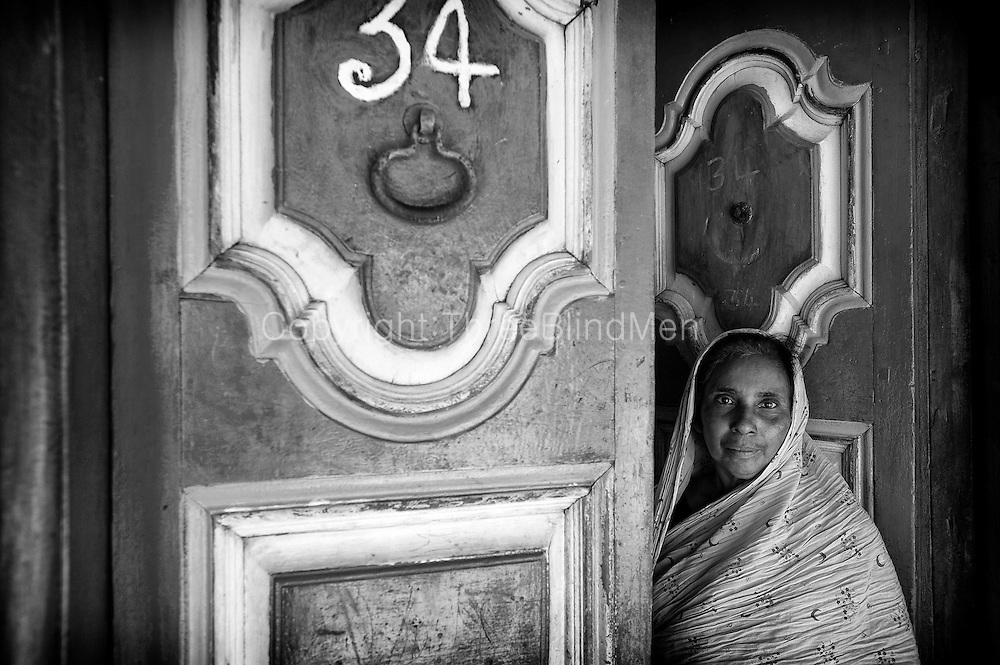 Distinctively painted front door. I like the clear house number '34'. Muslim woman at her home in Nagore. South India.