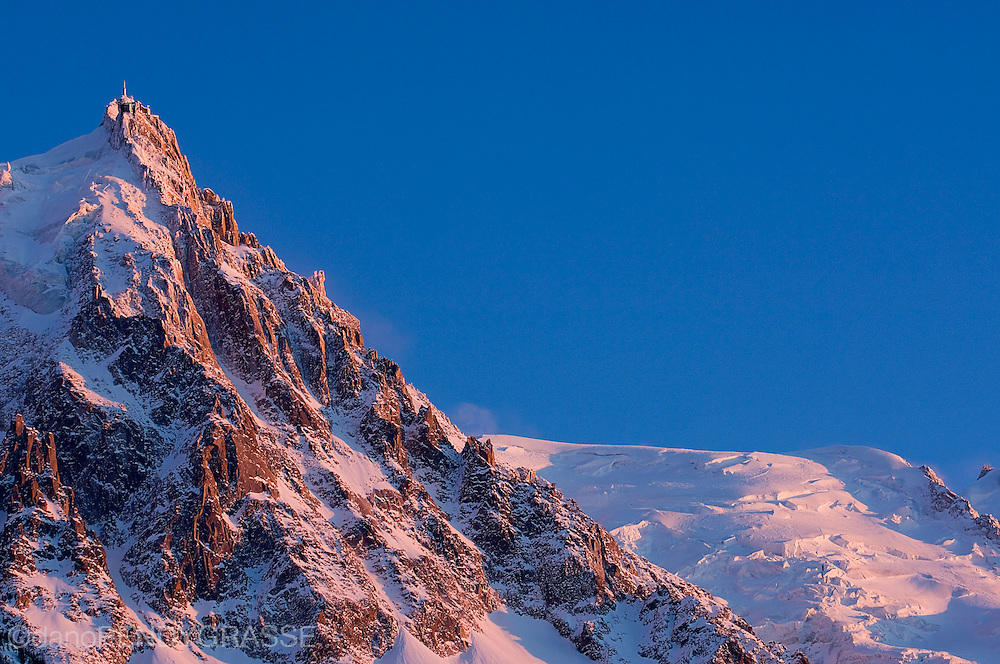 The aiguille du midi towers over Chamonix, France at sunset.
