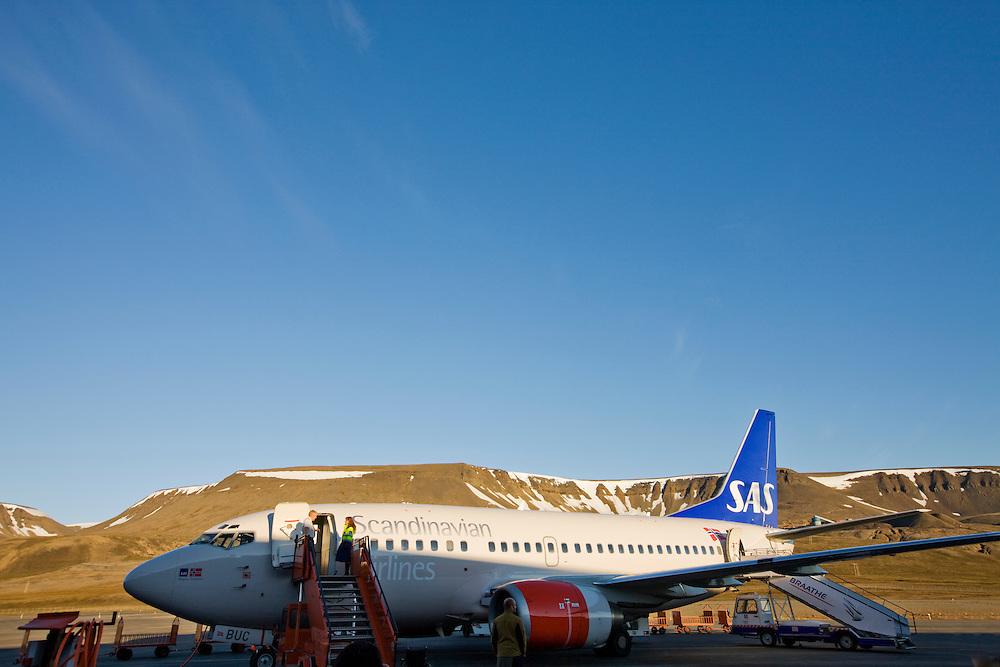 Norway, Svalbard, Longyearbyen, Midnight sun lights SAS Airbus 320 jet on runway after arrival