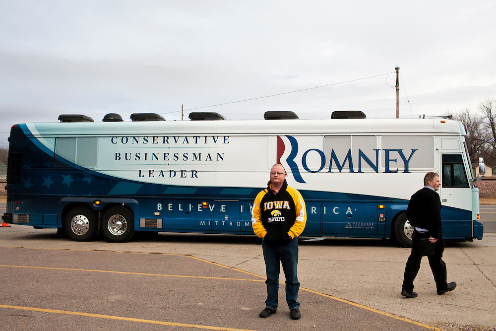 A man watches as Republican presidential candidate Mitt Romney meets with voters outside the Family Table restaurant on Saturday, December 31, 2011 in Le Mars, IA.