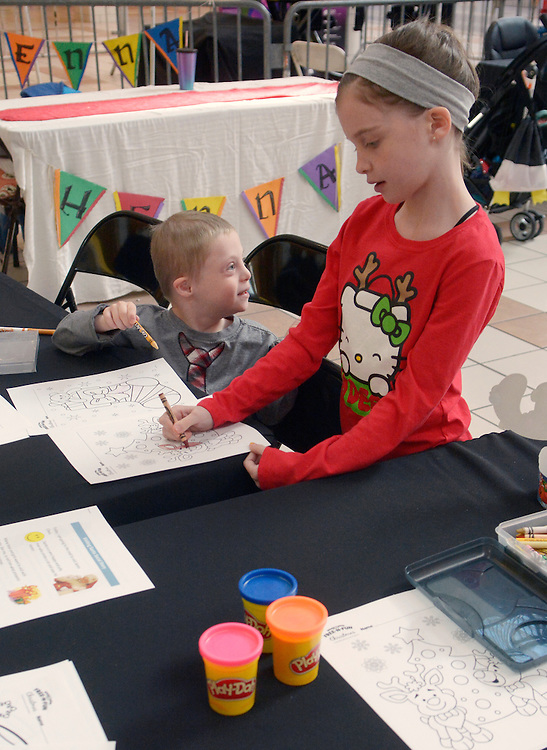 gbs120416g/ASEC -- Brody Willett, 6, and his sister, Brynn Willett, 8, of Albuquerque, use crayons to color during the Sensitive Santa event at Cottonwood Mall on Sunday morning, Dec. 4, 2016. The RSVP event before regular mall hours provided children with special needs and their families with a sensory friendly environment to safely experience the tradition of visiting Santa Claus. (Greg Sorber/Albuquerque Journal)