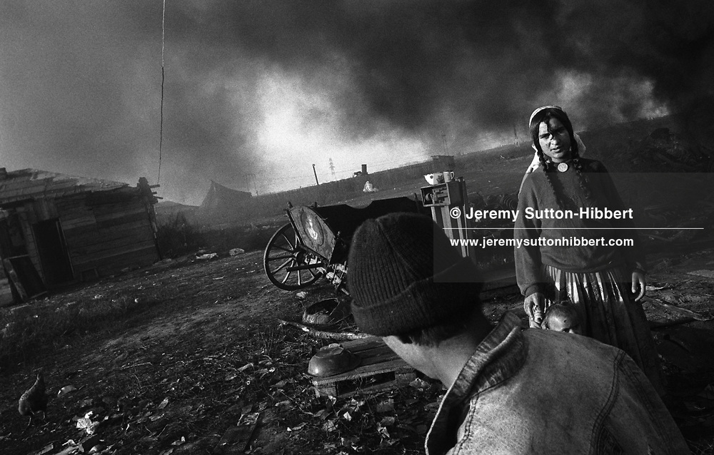 Smoke from a metal furnace hangs over the Kalderash Roma camp of Sintesti, near Bucharest. The furnace is owned by a family, melting scrap metal into pure ingots for resale.