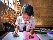 03 AUGUST 2015 - KATHMANDU, NEPAL:  A girl studies in a temporary school in central Kathmandu. Parts of her existing school were damaged in the earthquake and officials are afraid to use the existing structure, so they have set up a temporary school made of woven matting. The Nepal Earthquake on April 25, 2015, (also known as the Gorkha earthquake) killed more than 9,000 people and injured more than 23,000. It had a magnitude of 7.8. The epicenter was east of the district of Lamjung, and its hypocenter was at a depth of approximately 15 km (9.3 mi). It was the worst natural disaster to strike Nepal since the 1934 Nepal–Bihar earthquake. The earthquake triggered an avalanche on Mount Everest, killing at least 19. The earthquake also set off an avalanche in the Langtang valley, where 250 people were reported missing. Hundreds of thousands of people were made homeless with entire villages flattened across many districts of the country. Centuries-old buildings were destroyed at UNESCO World Heritage sites in the Kathmandu Valley, including some at the Kathmandu Durbar Square, the Patan Durbar Squar, the Bhaktapur Durbar Square, the Changu Narayan Temple and the Swayambhunath Stupa. Geophysicists and other experts had warned for decades that Nepal was vulnerable to a deadly earthquake, particularly because of its geology, urbanization, and architecture.    PHOTO BY JACK KURTZ