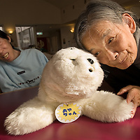 Elderly woman at a day care for older Japanese citizens playing with Paro,a robotic seal used to give comfort to the elderly.