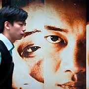 CHINA (Hong Kong). 2009. A man walking in front of a advertisement in Hong Kong.