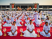 "11 FEBRUARY 2016 - KHLONG LUANG, PATHUM THANI, THAILAND:  People pray during the Makha Bucha Day service at Wat Phra Dhammakaya.  Makha Bucha Day is a public holiday in Cambodia, Laos, Myanmar and Thailand. Many people go to the temple to perform merit-making activities on Makha Bucha Day, which marks four important events in Buddhism: 1,250 disciples came to see the Buddha without being summoned, all of them were Arhantas, or Enlightened Ones, and all were ordained by the Buddha himself. The Buddha gave those Arhantas the principles of Buddhism. In Thailand, this teaching has been dubbed the ""Heart of Buddhism."" Wat Phra Dhammakaya is the center of the Dhammakaya Movement, a Buddhist sect founded in the 1970s and led by Phra Dhammachayo. Makha Bucha Day is one of the most important holy days on the Thai Buddhist calender.     PHOTO BY JACK KURTZ"