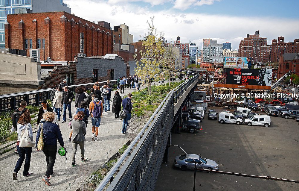 SHOT 5/4/14 2:27:09 PM - Locals and tourists stroll along the High Line in New York City, N.Y. The High Line (also known as the High Line Park) is a 1.45-mile-long New York City linear park built in Manhattan on an elevated section of a disused New York Central Railroad spur called the West Side Line. Inspired by the 3-mile (4.8-kilometer) Promenade plantée, a similar project in Paris completed in 1993, the High Line has been redesigned and planted as an aerial greenway and rails-to-trails park. New York is the most populous city in the United States and the center of one of the most populous urban agglomerations in the world—the New York metropolitan area. The city is referred to as New York City or the City of New York to distinguish it from the State of New York, of which it is a part. A global power city, New York exerts a significant impact upon commerce, finance, media, art, fashion, research, technology, education, and entertainment. New York City has often been described as the cultural and financial capital of the world. (Photo by Marc Piscotty / © 2014)
