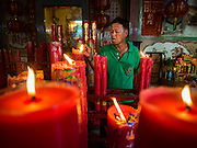04 FEBRUARY 2017 - BANGKOK, THAILAND:  A man lights prayer candles before a Chinese opera performance at the Phek Leng Keng Shrine in the Khlong Toey section of Bangkok. Many Chinese shrines and temples host Chinese operas during the Lunar New Year. Lunar New Year was January 28 this year and opera troupes are finishing their holiday engagements at the local temples.     PHOTO BY JACK KURTZ