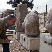 Der Spiegel correspondent Dr. Rainer Traub examines artifacts retrieved from the submerged palace complex of Egyptian Queen Cleopatra  on display February 02, 2012 at the Kom el Dekka archeological park in Alexandria, Egypt.  (Photo by Scott Nelson)