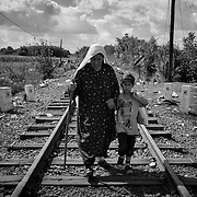 An elderly syrian refugee and her granddaughter cross the hungarian border from Serbia, on september 12, 2015. Thousands of refugees, most of them from Syria, cross this border everyday with the hope to reach european countries like Sweden or Germany. The next step for them will be to register in Hungary before continuing their long journey.