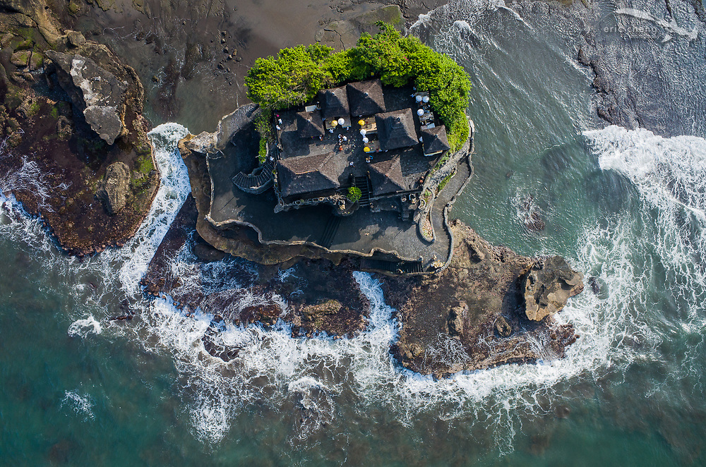 Aerial view of the pilgrimage temple Pura Tanah Lot, one of the seven sea temples in Bali. The temple is completely surrounded by water, and is accessible only to the Balinese. Bali, Indonesia.