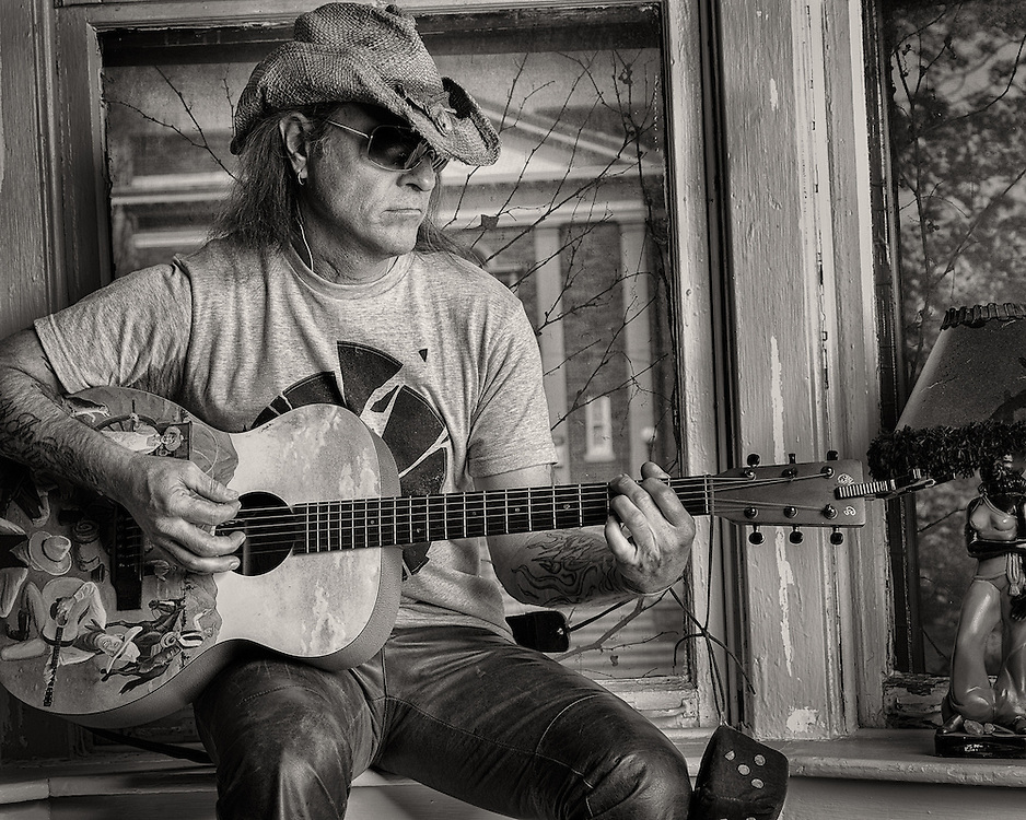 Scott Mertz playing the guitar at his home in Louisville.