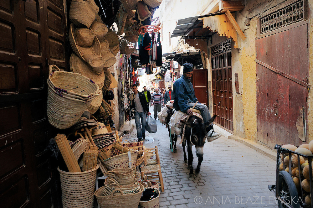 Morocco, Fez. Man riding a donkey in the street of the medina.