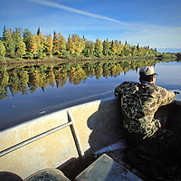 Subsistence hunter searches the bank during a fall moose hunt along the Kuskokwim River near Aniak