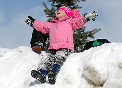Finley Peightal, 4, plays atop a pile of snow on East Deloney Ave. on Friday morning with her preschool class.