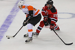 Jan 22, 2013; Newark, NJ, USA; Philadelphia Flyers center Claude Giroux (28) skates with the puck while being defended by New Jersey Devils left wing Mattias Tedenby (21) during the second period at the Prudential Center.