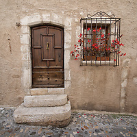 Wooden doorway and window with red flowers in St. Paul-de-Vence in the South of France